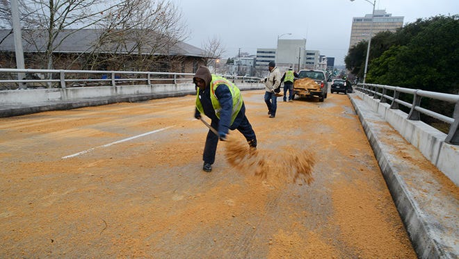City crews spread a layer of sand across the Pearl Street Bridge in Jackson Tuesday icy roads confront area motorists.