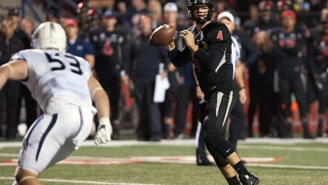 Fresno State Bulldogs quarterback Derek Carr (4) drops back for a pass against the Nevada Wolf Pack during the first quarter at Bulldog Stadium.