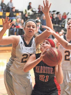 HLV's Emma Cheney is surrounded by three Sigourney players as she eyes the basket in a Dec. 22 game at Sigourney. Cheney scored 15 points and grabbed 16 rebounds in a losing cause, 48-40.