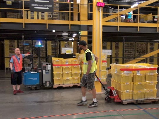 Amazon workers in Robbinsville Fulfillment Center move around orders.