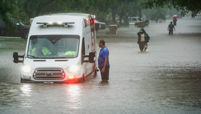 Residents of a McAllen, Texas, neighborhood walk down a flooded street that trapped an ambulance during a second day of heavy rains and street flooding, on June 21, 2018.
