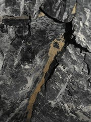 A mined through hydraulic fracture in the Fruitland Coal shows a one-inch wide crack held open by frack sand.