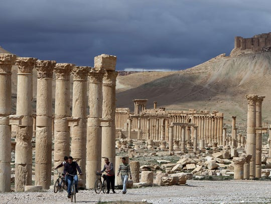 Syrian citizens ride their bicycles near ruins in the
