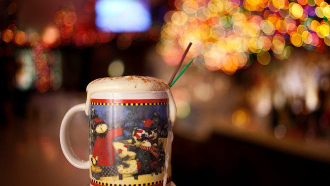 A Tom and Jerry is surrounded by Christmas lights on the bar Friday at the Brass Rail in downtown Port Huron.