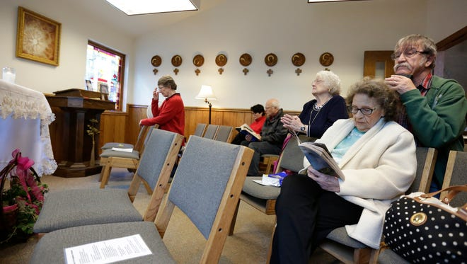 A group of parishioners pray Tuesday in the Adoration Chapel of Saint Therese Catholic Church in Rothschild.