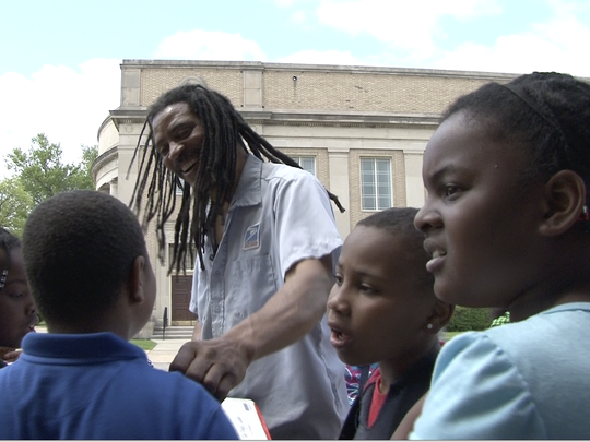 """The subject of """"Detroit 48202"""" Wendell Watkins is seen in the film taking children from the Boggs School on a walking tour of his postal route in 2015."""