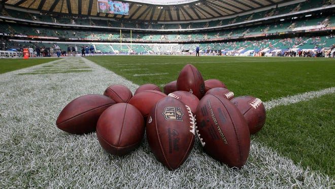 A pile of footballs are placed on the touchline during the warm-up before an NFL football game between New York Giants and Los Angeles Rams at Twickenham stadium in London, Sunday Oct. 23, 2016.