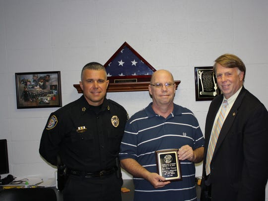 Sgt. Mike Thomas (center) receives an Employee of the Month award from Jackson Police Chief Julian Wiser (left) and Madison County Sheriff John Mehr (right).