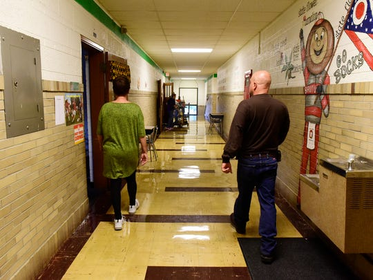 Beth Shilling, custodian at Croghan Elementary, left, and Don Jacobs, maintenance worker with Fremont City Schools walk down the hallway.