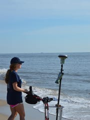 Shannon Emrich, a University of Delaware sophomore engineering student, measures a beach with a GPS unit to track changes in slope over time.