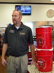 Andy Yergensen, franchise owner of St. George's Firehouse Subs, talks Tuesday about the pickle containers the company accepts donations for. The funds go to the Firehouse Subs Public Safety Foundation, which then distributes it in the form of equipment to public safety organizations.