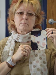 Cindy Ryder holds a photo of her Chihuahua, Bartok, who was killed during an attack by a neighbor's pit bull June 19.