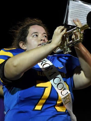 Abby Breitner wears her football uniform and homecoming court sash as she plays with the band at Ida's homecoming game last week.
