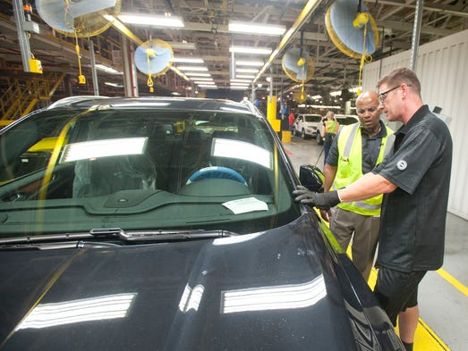 Daryl Sykes, plan manager of The Ford Motor Company's Louisville Assembly plant, left, talked to Eric Lyle, a Lincoln Validation Center fitter, as Ford's newly unveiled luxury Lincoln SUV, the MKC, rolled down the finishing line at the plant. 25 August 2014