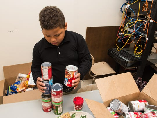Second-grader Jayden Joseph gathers cans at the Marion