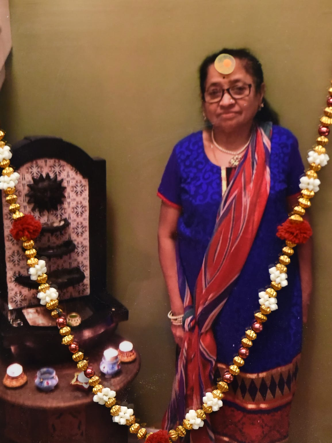 Beads adorn this photo of Rekhaben Shah on her family's memorial altar. Shah, 67 died after she stopped breathing during a routine colonoscopy at Oak Tree Surgery Center in Edison, NJ.