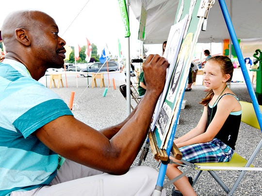 """Artist Mel Conrad, left, of York, creates a caricature of Kiana Horton, 9, right, of Dover, during the 15th Annual Penn-Mar Irish Festival at the Markets at Shrewsbury in Glen Rock, Pa. on Saturday, June 20, 2015.  Dawn J. Sagert - dsagert@yorkdispatch.com"""