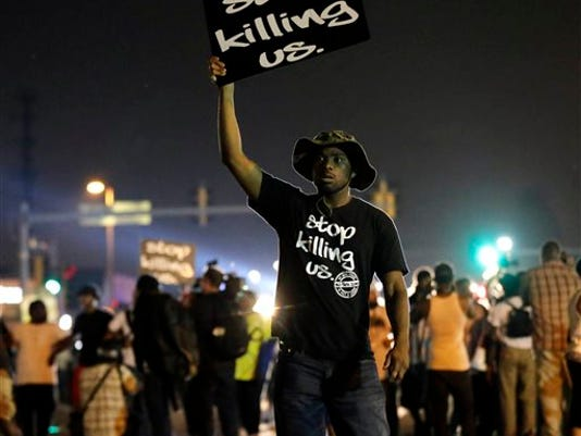 In this Aug. 18, 2014, file photo, protesters walk through the streets after a standoff with police in Ferguson, Mo. A year ago, most Americans had never heard of the St. Louis suburb called Ferguson. But after a white police officer fatally shot a black 18-year-old in the street, the name of the middle-class community quickly became known around the world.