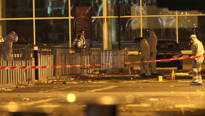 Investigating police officers work outside the Stade de France stadium in Saint Denis, outside Paris on Friday. Multiple fatal attacks throughout the city prompted President Francois Hollande to announce he was closing the country's borders and declaring a state of emergency.