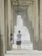 Scott Crawford snaps a photo of waves under pier after Hurricane Nate in Pensacola.