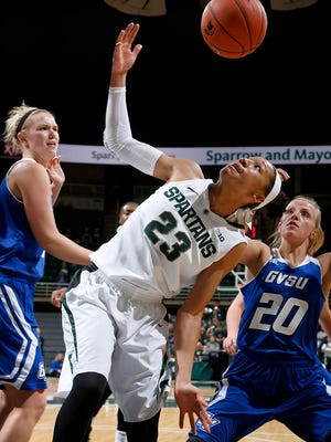 Michigan State's Aerial Powers (23) reaches for a loose ball between Grand Valley State's Janae Langs (20) and Piper Tucker, left, Sunday.
