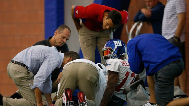 New York Giants wide receiver Odell Beckham Jr. is looked after by medical staff after injuring his leg during practice at the team's NFL football camp, Sunday, July 31, 2016, in East Rutherford, N.J.