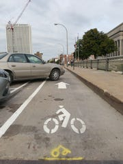 A car parks into a bike lane along 3rd Street in Cedar Rapids, Iowa, on Tuesday, Sept. 22, 2015. Some riders feel safe by the protected bike lane along the street downtown, but others feel the slanted parking can cause hazards.