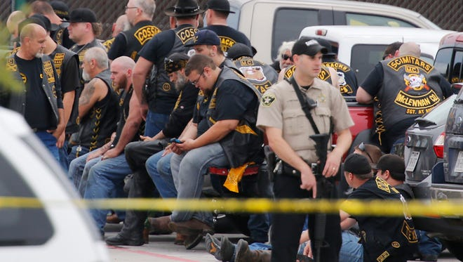 """A McLennan County deputy stands guard near a group of bikers in the parking lot of a Twin Peaks restaurant Sunday, May 17, 2015, in Waco, Texas. Waco Police Sgt. W. Patrick Swanton told KWTX-TV there were \""multiple victims\"" after gunfire erupted between rival biker gangs at the restaurant. (Rod Aydelotte/Waco Tribune-Herald via AP)"""