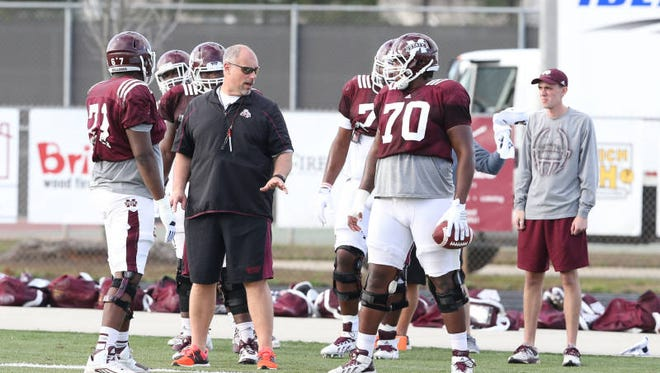 Mississippi State's Justin Malone (70) works with offensive line coach John Hevesy at center during Saturday's practice.