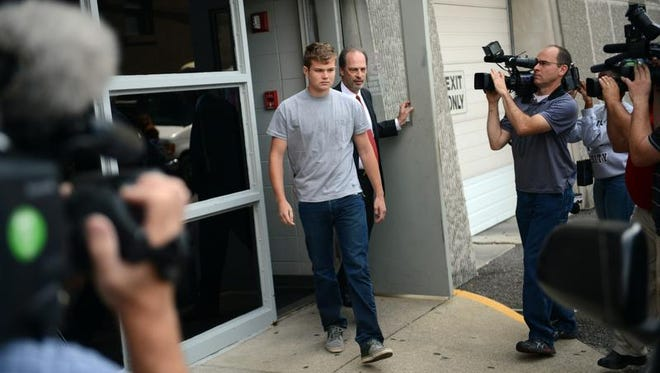 Speck Mellencamp, center, leaves the Monroe County Jail after being booked into and bonded out of jail in Bloomington, Ind., Friday, Aug. 16, 2013. Speck Mellencamp and his brother, Hud, 19, sons of rock star John Mellencamp, face felony battery charges stemming from a July incident during which police say they punched and kicked a 19-year-old man they assaulted on his front porch.