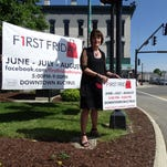 Sue Logdon sets out a sign in downtown Bucyrus in preparation for the city's upcoming First Fridays event.