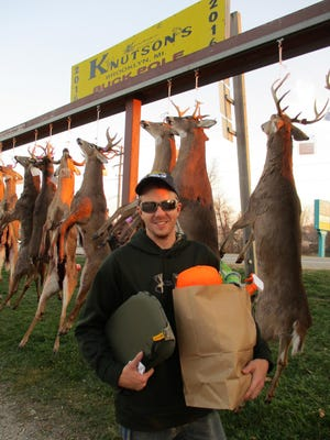 At Knutson's buck pole in Brooklyn, Sean Hawley of Napoleon stands in front of an eight-point buck he shot Tuesday.