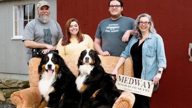 """Medway photographer Tim Rice, left, and his family - daughter Anna, son Dan and wife Barbara, and their dogs, Argus and Josie - in their own porch portrait. Rice, with help from Barbara, recently drove around town to capture photos of socially distanced families on their porches and in their yards and driveways for the """"coronavirus series"""" of his We Are Medway project. In the process, the couple colleted hefty donations for the town's two food pantries."""