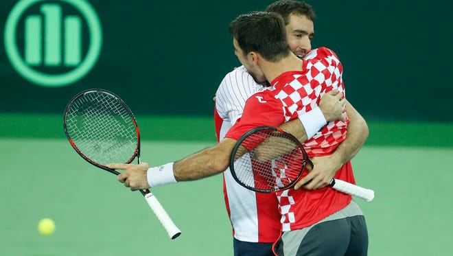 Croatia's Marin Cilic, left, celebrates with Ivan Dodig after defeating Argentina's Juan Martin Del Potro and Leonardo Mayer in their Davis Cup finals tennis doubles match in Zagreb, Croatia.