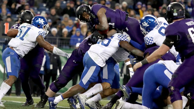Northwestern running back Justin Jackson (21) leaps over the pile for a touchdown during the second quarter of the Music City Bowl at Nissan Stadium in Nashville, Tenn., Friday, Dec. 29, 2017.