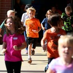 First grader Alex Fyfe wears a pumpkin t-shirt while running in the Great Pumpkin Fun Run at Myers Elementary School, Tuesday, Oct. 6, 2015, in West Salem, Ore. The run teaches the students an active lifestyle and Halloween safety tips.