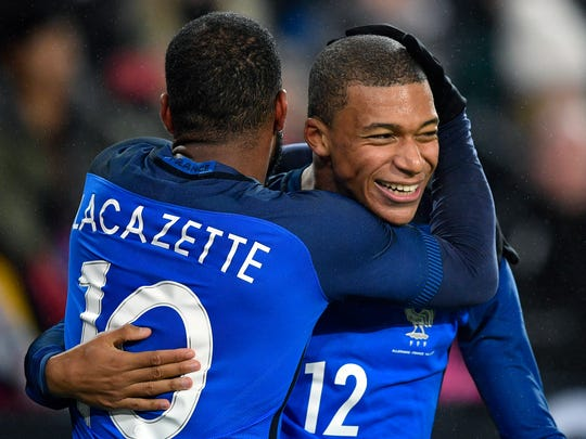 France's scorer Alexandre Lacazette, left, and his teammate Kylian Mbappe, right, celebrate their side's 2nd goal during an international friendly soccer match between Germany and France in Cologne, Germany, Tuesday, Nov. 14, 2017. (AP Photo/Martin Meissner)