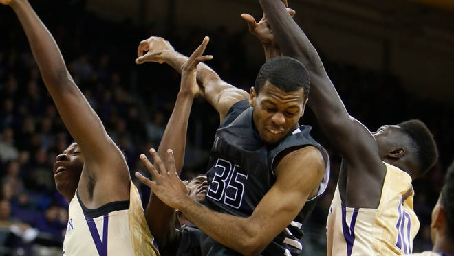 Oakland guard Martez Walker (35) goes for a rebound between Washington forward Noah Dickerson (left) and forward Malik Dime during the second half Saturday in Seattle.