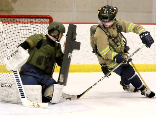 Milwaukee Admirals forward Tyler Moy in firefighting gear goes against Admirals goalie Jake Paterson in police tactical gear for promotional photos for the Battle of the Badges hockey game between area police and fire departments personnel at the Panther Arena on March 4.