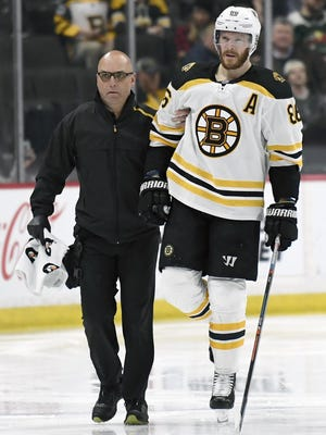 The Bruins' Kevan Miller skates off the ice with a trainer after suffering a fractured kneecap against the Minnesota Wild on April 4, 2019.