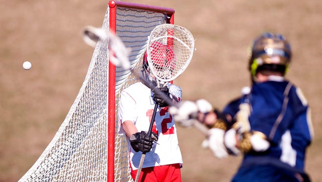 An Essex attacker fires a shot wide of Champlain Valley goalie Andrew Tieso (12) during Tuesday's boys lacrosse game in Hinesburg.