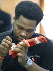 Vertus Charter School 10th-grader Justin McGill adds wires to a prosthetic hand made with a 3-D printer.