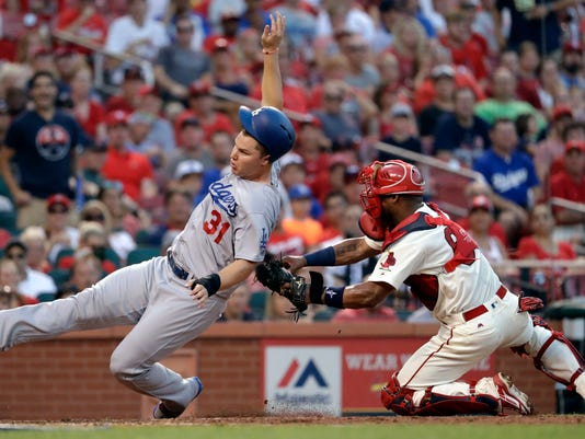 Los Angeles Dodgers' Joc Pederson, left, is tagged out at home by St. Louis Cardinals catcher Alberto Rosario during the sixth inning of a baseball game Saturday, July 23, 2016, in St. Louis. (AP Photo/Jeff Roberson)