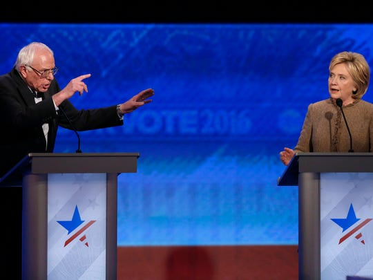 Bernie Sanders, left, and Hillary Clinton speak during an exchange during the Democratic presidential primary debate Saturday, Dec. 19, 2015, at St. Anselm College in Manchester, N.H.