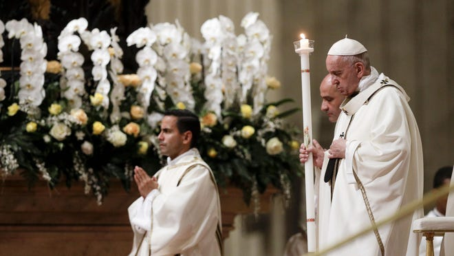 Pope Francis holds a candle as he presides over a solemn Easter vigil ceremony in St. Peter's Basilica at the Vatican, Saturday, April 21, 2019.