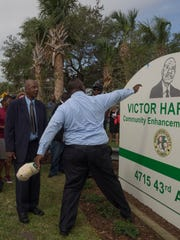 Victor Hart Sr. is shown the new sign for the park by his son Victor Hart Jr.