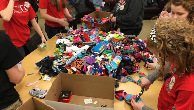 Students at Pinckney High School and Pathfinder Schools held a wacky sock drive for the children of Mott Children's Hospital. Together the two schools collected over 700 pairs of new socks. Eight students were given the opportunity to deliver the sock to Mott's and see how their work and efforts were appreciated by many of the patients. Clockwise from left are eighth graders Sarah Dorosh and Ashley Fransee, ninth grader Reece Ohmer and seventh grader Olivia Ohmer.