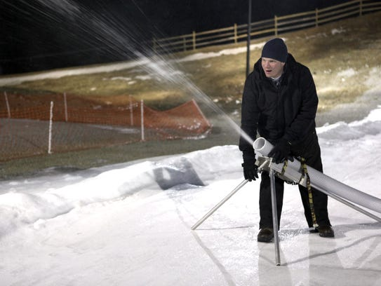 Ryan Suhr repositions the snow blowing hose.