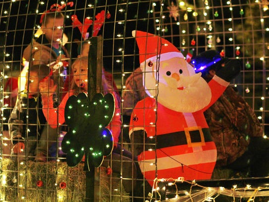 Santa Claus and his young elves were draped in lights.