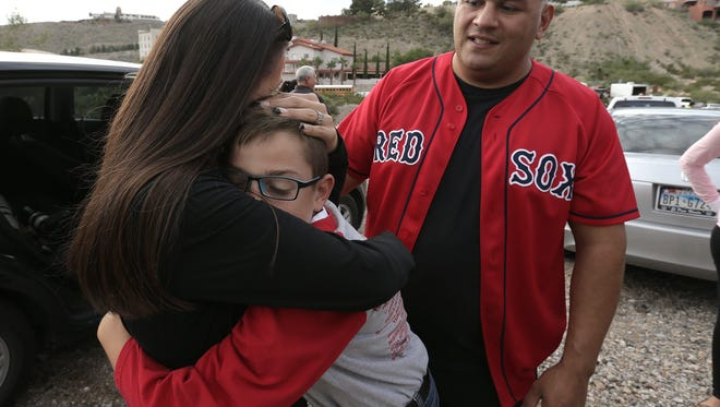 Socorro MIddle School student Joshua Acres hugs his mother Monica Figueroa after being rescued from the Wyler Aerial Tramway Friday. Joshua was met by his mother and father Joel Figueroa, right.